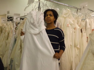Julie Young of Windfall Basics, a non-profit agency in Etobicoke, shows one of many wedding and Prom dresses for sale starting on April 24. They are all brand new and are donated by big name stores.